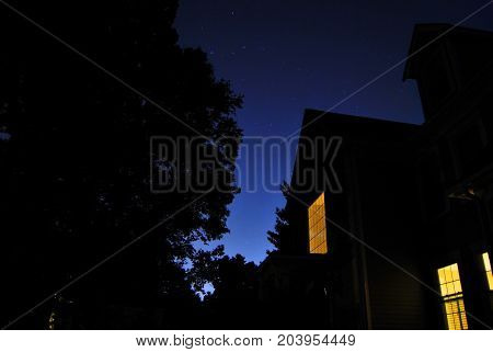 Bright beautiful blue sky with silhouette of house and trees, yellow lights on in house, stars in the sky