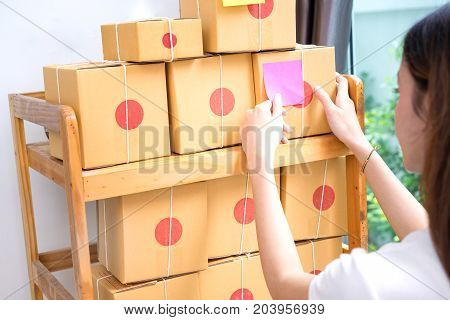 Young asian girl freelancer business owner taking post it to box working at home office with note packaging delivery market on purchase orders to customer.