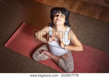 Pregnancy Yoga and Fitness concept. Healthy maternity lifestyle concept. 40 week pregnant middle aged caucasian woman sitting in lotus asana doing yoga exercises and showing signs ok with her arms.