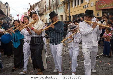April 14 2017 CotacachiEcuador: indigenous quechua playing flute made of bamboo at the Easter procession while walking n the street