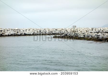 Breakwater made of boulders granite rocks and round concrete blocks along entrance banks to Ventura harbor port of San Buenaventura Southern California