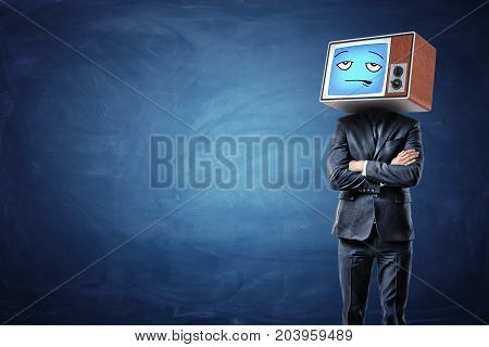 A businessman with folded hands and an old TV on his head showing a blue bored emoticon. Business meetings. Tired of office routine. Unmotivated personnel.