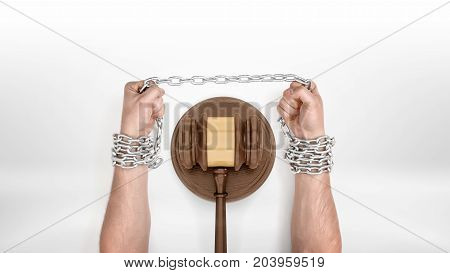 Strong male hands straining a metal chain capturing them around a judge gavel. Legal help. Debt and credit strain. Declaring bankruptcy.