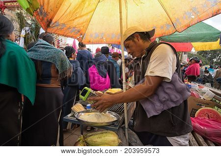 April 14 2017 CotacachiEcuador: man is grating cheese at a food stand on the edge of the indigenous kechwa crowd at the Easter procession