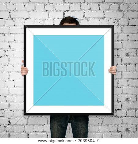 man holding square frame on brick background