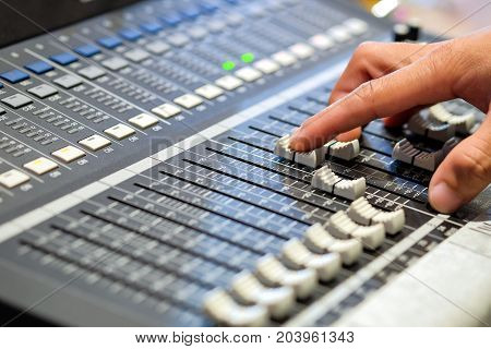 Sound engineer's fingers are pressing the button audio controller in recording room.