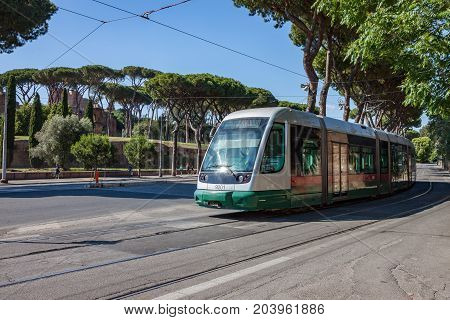 A modern electric streetcar passing through Rome near the Colosseum