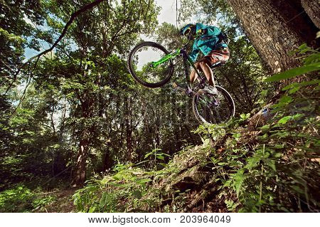 Moscow Russia - August 18 2017: Mountain bike cyclist doing wheelie stunt on a mtb bike. Mountain Bike cyclist riding in forest. Biker riding extreme sport bicycle. Cool athlete cyclist on a bike. MTB biking.