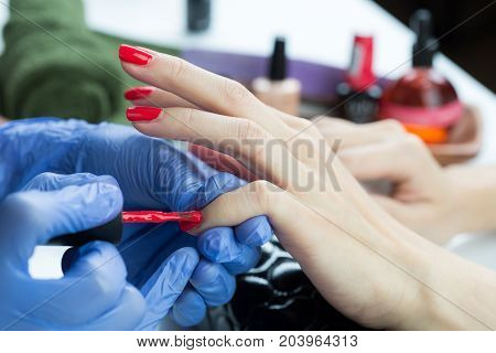 Manicure and pedicure series: Manicurist applying nail polish on customer's nail