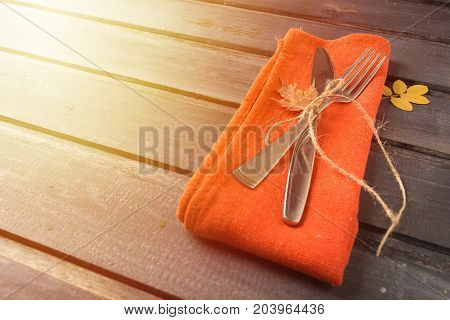 Fall Serving Perspective Table With Fork, Knife And Napkin Over Wooden Background