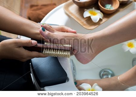 Manicure and pedicure series: Pedicurist brushing customer's foot in pedicure bowls