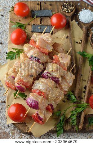 Raw chicken kebabs on a brown background
