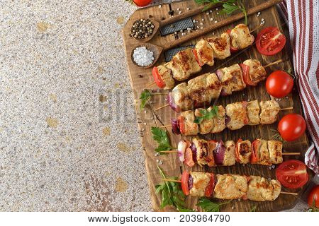 Chicken kebabs with vegetables on a brown background