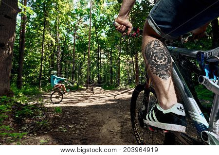Moscow Russia - August 26 2017: Cyclist with tattoo on leg siting on mtb bike in forest. Cool athlete cyclist on a bike. MTB biking.