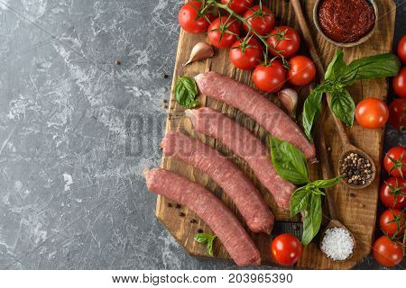 Natural raw sausages with basil and tomatoes on a gray background