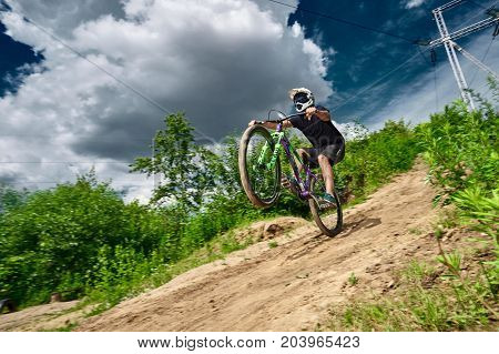 Moscow Russia - July 6 2017: Mountain bike cyclist doing wheelie stunt on a mtb bike. Biker riding extreme sport bicycle. Cool athlete cyclist on a bike. MTB biking.