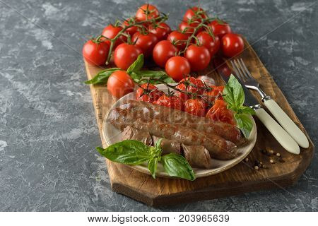Fried sausages with tomatoes on a gray background