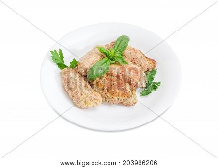 Braised meat roulades with filling from bread dried crusts and mushrooms decorated with basil and parsley twigs on a white dish on a white background