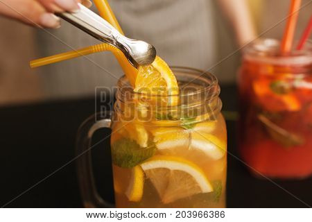 Waiter preparing orange fruit cocktails. Fresh citrus and strawberry cold drink with mint and ice on table, concept refreshment and satisfying thirst in summer, close up picture