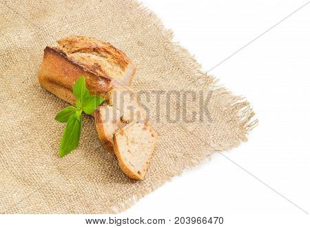 Partially cut wheat sourdough bread with basil twig on a sackcloth on a white background