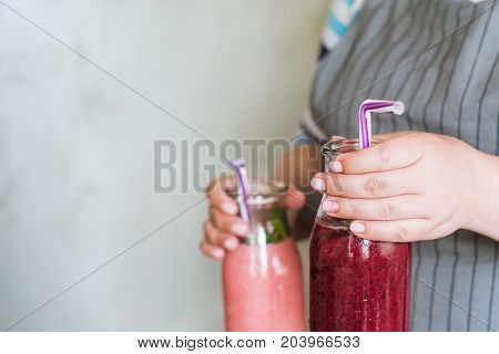 Waiter brings bottles of smoothie in hands. Fruit drinks from strawberry and wineberry with mint, refreshment in summer period and healthy cocktails, detox, smart food close up picture
