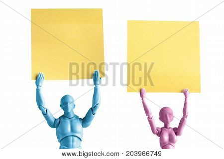 Male and female figurines extreme closeup holding up yellow blank papers above their heads isolated on white with copy space