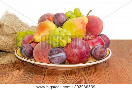 Pile of the apples pears plums peaches and clusters of white grapes on the big yellow dish on a surface of old wooden planks with sackcloth on a white background