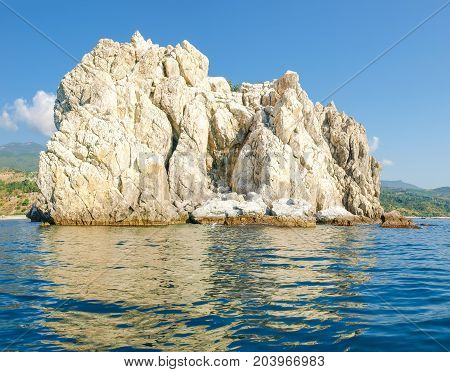 Single limestone rock in the sea on the background of the shore with the mountain slopes and the sky