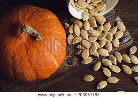 Bowl With  Dried Pumpkin Seeds And A Little Pumpkin On A Brown Table, Top View