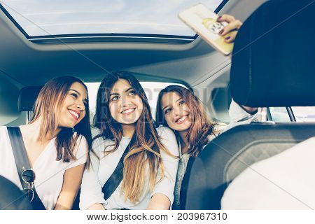 Group of girls friends making a selfie sitting on the back of a car on a journey