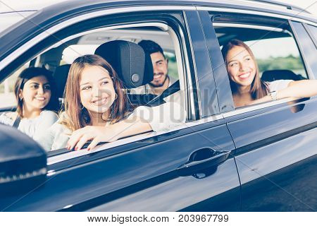 Young woman is driving a car with her friends on journey