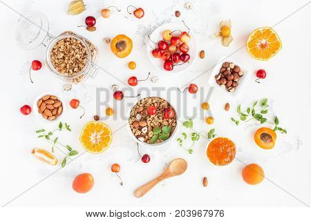 Breakfast with muesli fruits berries nuts on white background. Healthy food concept. Flat lay top view.