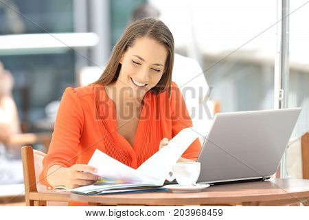 Single entrepreneur working reading documents sitting in a bar terrace
