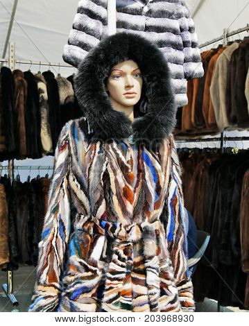 Fashionable hooded fur coat on mannequin retail shopping. Luxury fur coats hanging on rack in the background.
