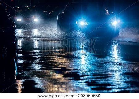 Cars Driving In Night City Through Big Water Puddles With Blue Headlights