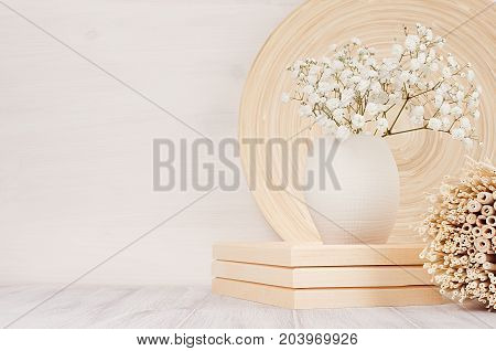 Soft home decor of beige bamboo dish twigs and white small flowers in ceramic vase on white wood background. Interior.