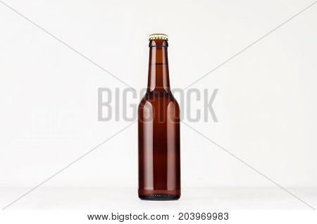 Brown longneck beer bottle 330ml mock up. Template for advertising design branding identity on white wood table.