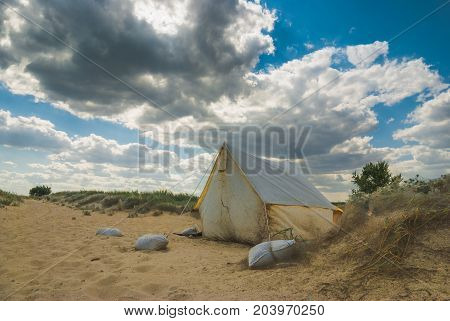Old tourist tent on a sea beach.
