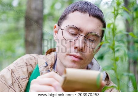 Image of dark-haired biologist in glasses writes in notebook at forest among plants and trees in summer afternoon