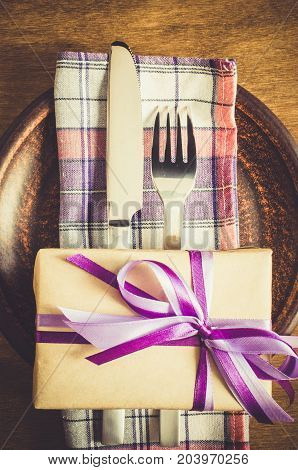 Festive Table Setting. Cutlery with Present on Linen Napkin on Rustic Wooden Background. Father's Day Concept. Copy Space. Selective Focus.
