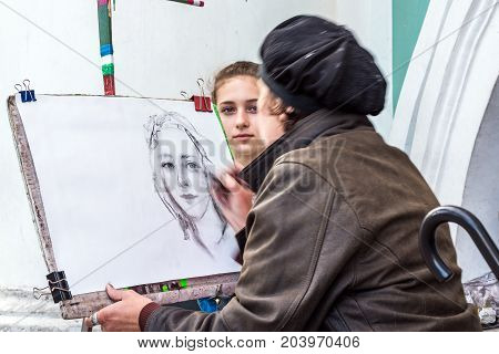 ST.PETERSBURG/RUSSIA - JULY 23, 2017. City artist draws a portrait of a girl on the street of St. Petersburg
