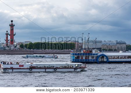 ST.PETERSBURG/RUSSIA - JULY 23, 2017. Pleasure boats near the Spit of Vasilievsky Island with rostral columns - one of the sights of St. Petersburg