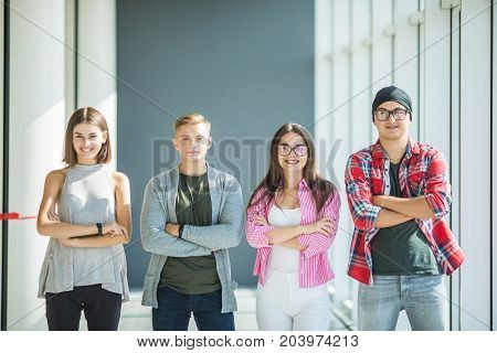 Four Friends Standing With Crossed Hands And Smiling Indoors. Fours Students In University.
