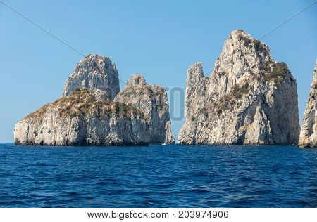 View from the boat on the Faraglioni Rocks on Capri Island Italy.
