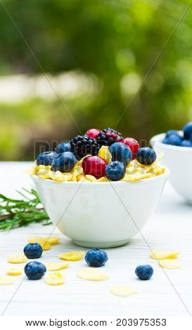 A useful breakfast in the garden on a white table. Forest berries and corn flakes.