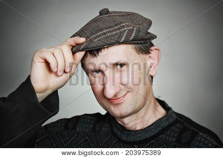 Portrait of funny real man in a cap and sweater on a gray background. Hand on the cap