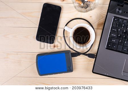 Flat Lay Above Lap Top Computer On The Wooden Table With External Hard Disc Hdd Mobile Phone Cup Of