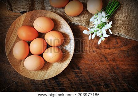 Easter background. Rustic wooden table with plate, egg, flowers and cutting board . Top view.
