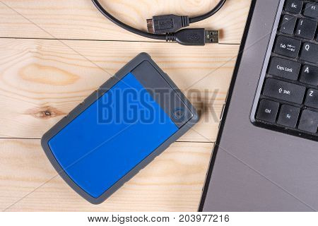 Flat Lay Above External Hard Disc By Lap Top Computer On The Wooden Table