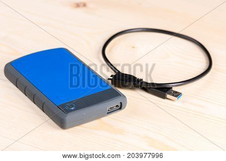 External Hard Disc Hdd With Usb Cable On The Wooden Board Table